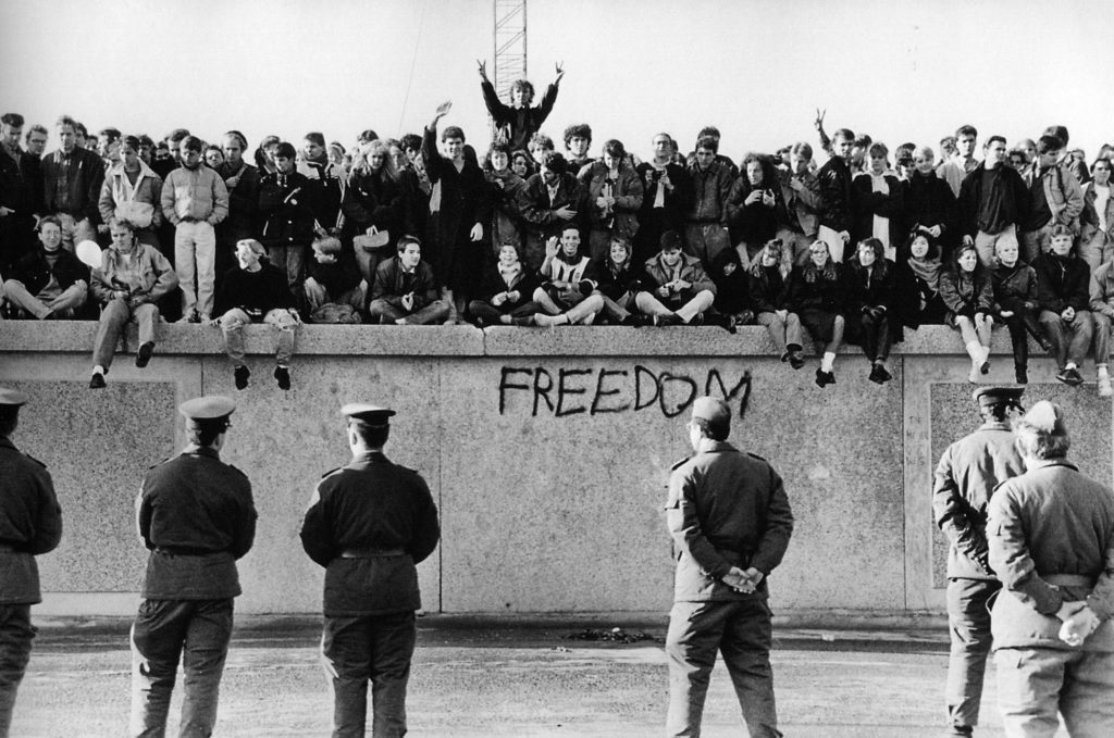 East German students climbing the Berlin Wall in 1989